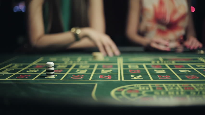 People placing bets for roulette in casino. Slider camera movement