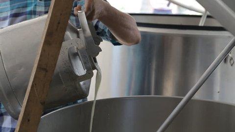 Milkman pouring milk in milk cooling tank