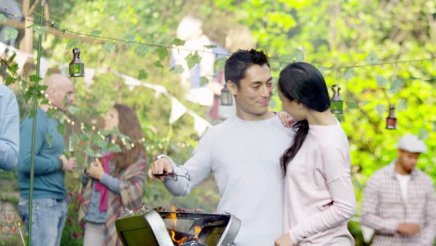 4K Happy Attractive Asian Couple Cooking At Bbq While Friends Socialize In The Background Shot