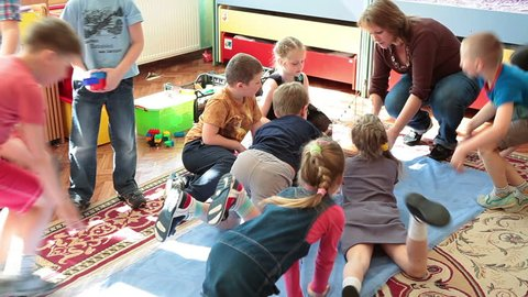 ST. PETERSBURG, RUSSIA - CIRCA MAY, 2015: Daycare assistant a woman plays with children active games in nursery. Russian kindergarten is a preschool educational institution