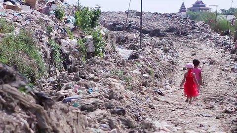Little children walk on landfills. Children from the poorest countries. Needy children.