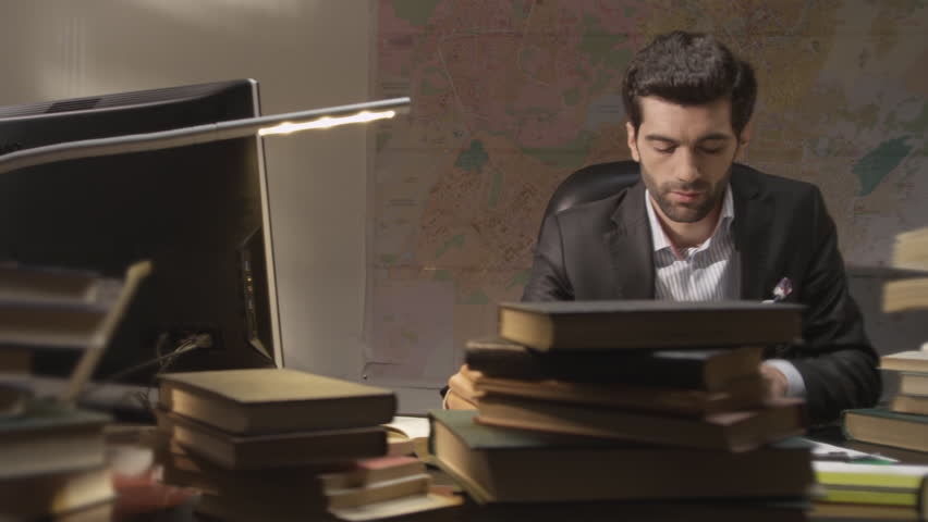 Businessman working and exploring books in the working room. Shot on RED EPIC Cinema Camera.
