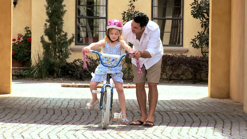 Asian father teaching his little blonde daughter to ride a bicycle