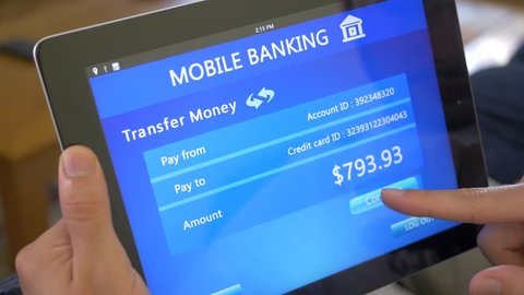 Transferring money founds with a mobile online banking application on a tablet device.