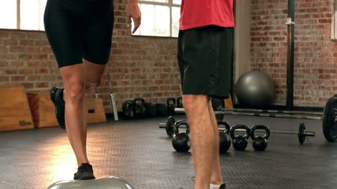 Trainer helping client balance on bosu ball in slow motion