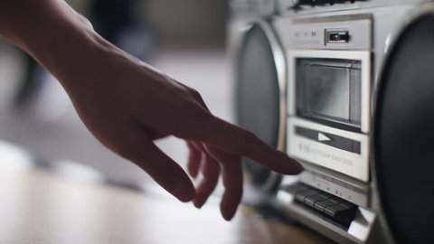 4K Close up of a female hand putting a music cassette into a retro stereo player and pressing play, shot on Red Epic