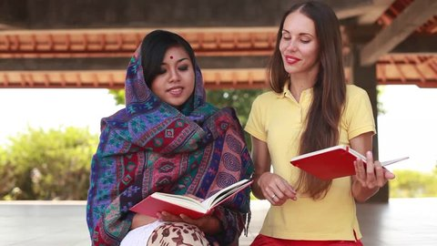 European woman volunteering in Nepal, teaching a poor asian woman to speak English language