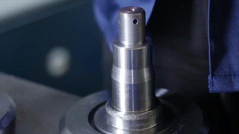 Industrial worker measure detail with digital caliper micrometer at factory workshop