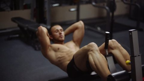 Young athletic man doing exercise in gym. Shallow depth of field. Abs crunches on bench. Loop