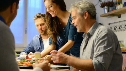 Young woman serving plate of cheese to man in kitchen. Happy friends eating together at home aperitif. Smiling men and woman eating together.