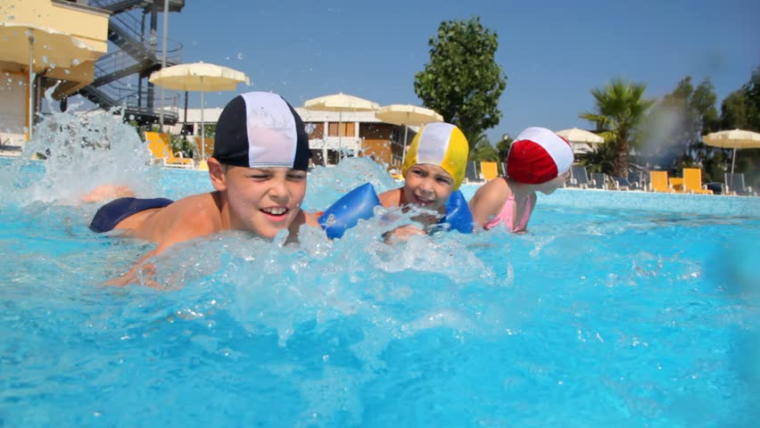 Boy and two girls in swimming caps are splashing water in the pool