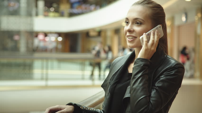 Beautiful girl with long hair, talking on the phone in the mall | Shutterstock HD Video #11817407