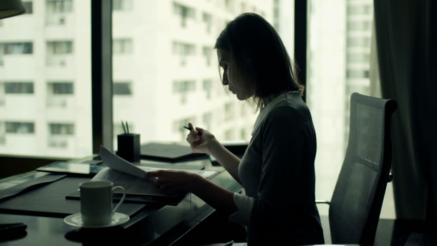 Young businesswoman writing notes in documents sitting by desk in office  | Shutterstock HD Video #11826947