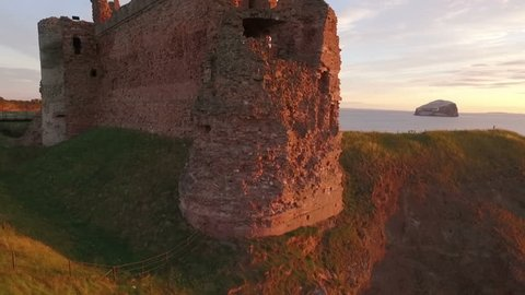 Stunning aerial shot Tantallon Castle off the coast of North Berick, Scotland with Bass rock in the background
