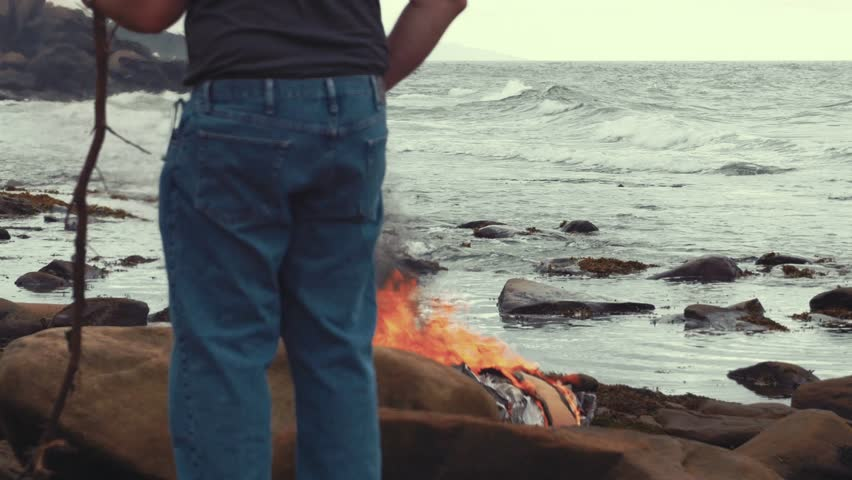 A man burning garbage and card board boxes on a rocky beach by the ocean   Shutterstock HD Video #11838857