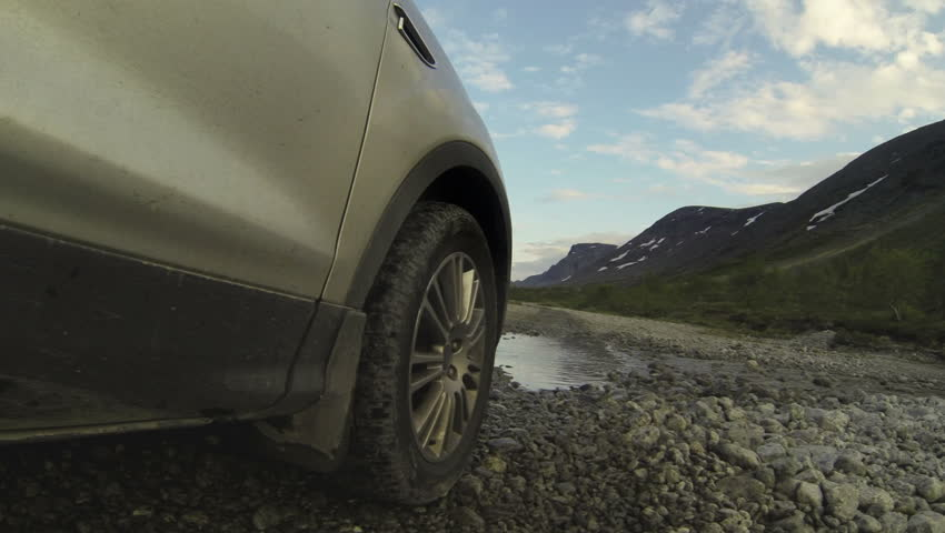 Pov, car driving across mountain river, tire riding on gravel road. Gopro. Khibiny, Russia