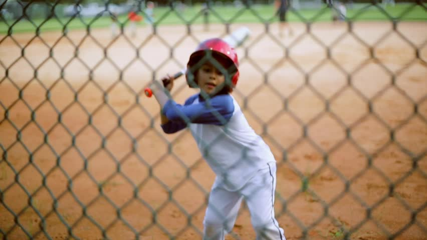 A really cute kid practicing his batting during baseball practice.  Shot from behind a fence