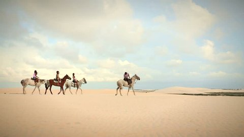People on a horseback ride / Girls riding horses in the desert