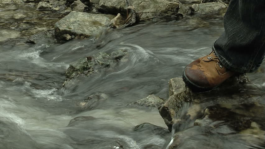 Person's shoe on rock in middle of a stream.  Slow shutter for smooth water effect.
