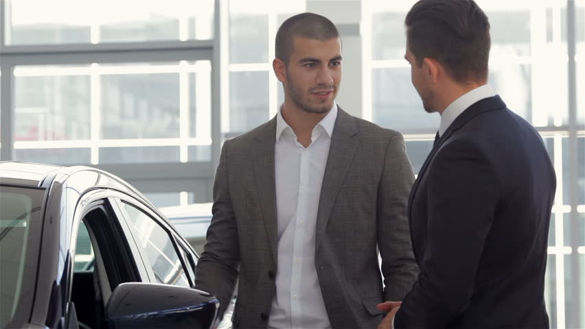 Car Showroom. Vehicle Dealer Showing Young Man New Car. Auto business, car sale, technology and people concept - happy male with car dealer in auto show or salon. Young man with a salesman in a motor | Shutterstock HD Video #11918783