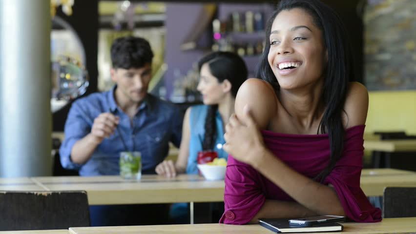 Closeup shot of young woman looking at camera. Happy african girl smiling  sitting at bar