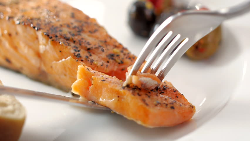 pick up grilled salmon from dish with olives and Baguette