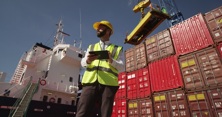 A young manager doing inspection rounds through an industrial harbor working on a digital tablet. Shot on RED Epic.
