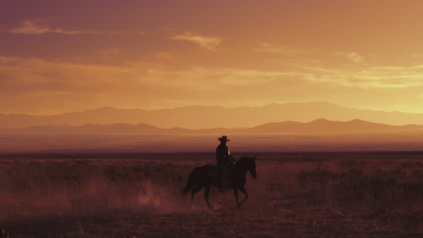 Slow motion shot of a cowboy riding a horse. This shot was taken at sunset on an open field with a mountain range in the background.
