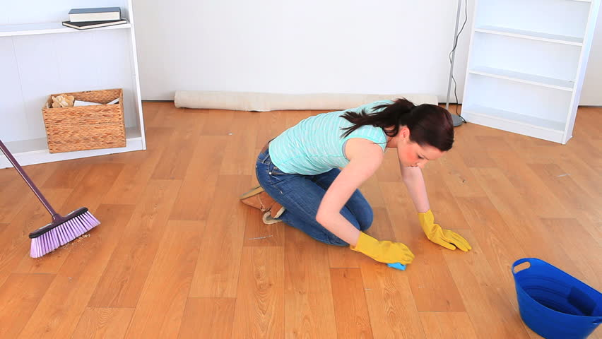 Young woman cleaning the floor of the living-room