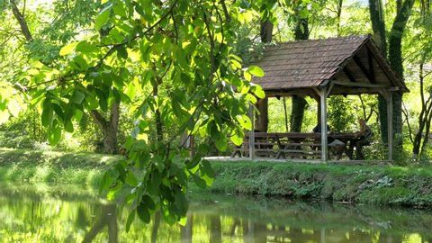 Summer house on the lake coast and two male person,young adult and elderly man sitting on the benches and talking,enjoy in vacation on magical place in nature,sunny day,daylight,leisure,tourists.