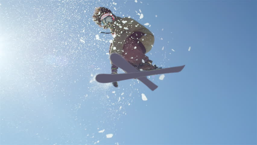 SLOW MOTION CLOSEUP: Freestyle skier jumping big kicker and flying over the sun in snowy mountains #12010307