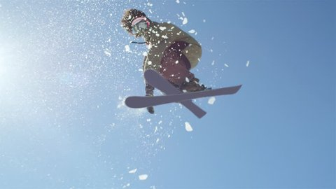 SLOW MOTION CLOSEUP: Freestyle skier jumping big kicker and flying over the sun in snowy mountains