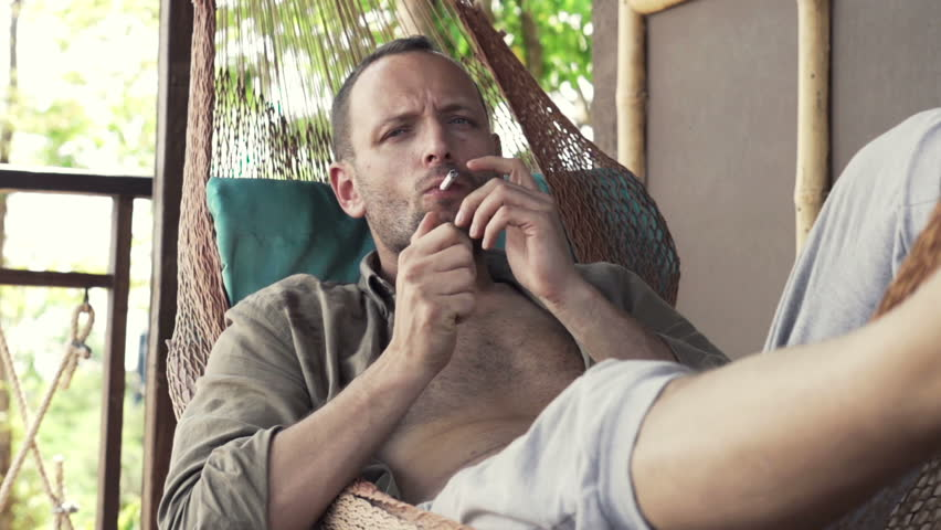 young man smoking cigarette lying on hammock   hd stock footage clip a pensive man sitting by a big bright window in a large lounge      rh   shutterstock