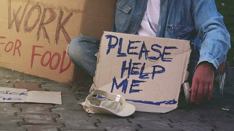 Homeless beggar asking for help, adult man begging on the street.