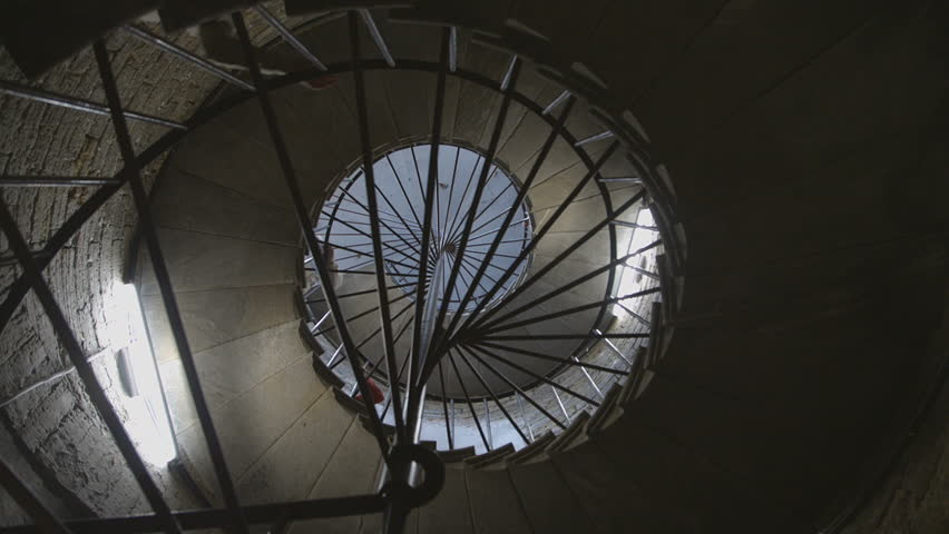 People climb the old spiral staircase in temple