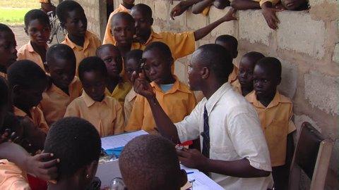 Kenya, Africa - April, 2013: Medium shot of teacher teaching kids