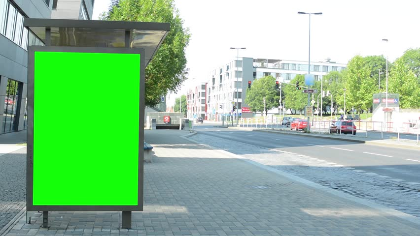 bus stop with green screen billboard in the tranquil part of the city - cars slowly pass around