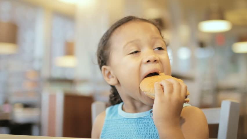 Child eating hamburger at fast food restaurant