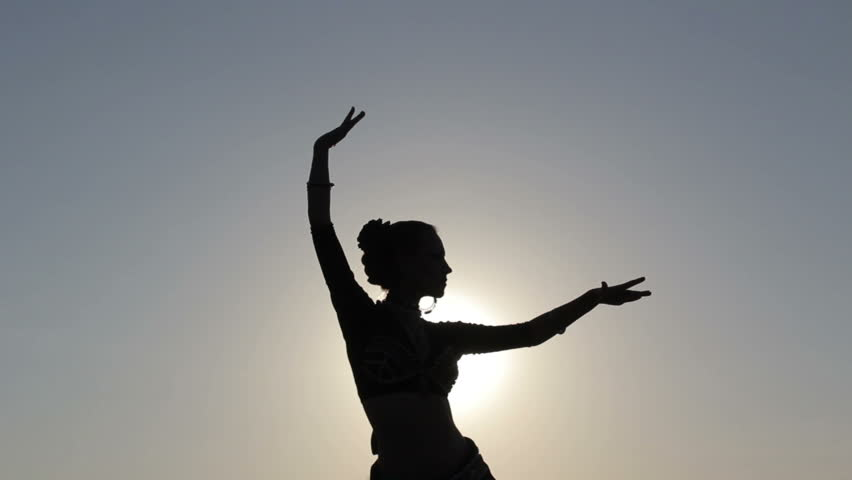 Silhouette girl oriental dancer masterly performing a dance on sky background