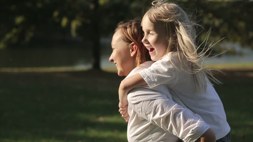 Daughter riding on mother in a city park at sunset. Slow motion | Shutterstock HD Video #12096125