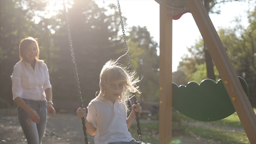 Mother pushing child on a swing set. Slow motion | Shutterstock HD Video #12097643