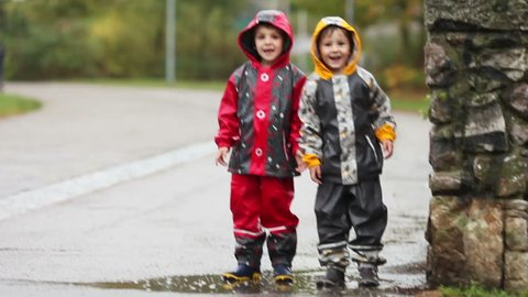 Two boys, brothers, jumping in muddy puddle in the park, autumn time on a rainy day