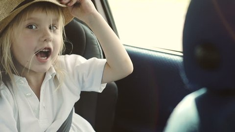 A child riding in the car played with straw hat