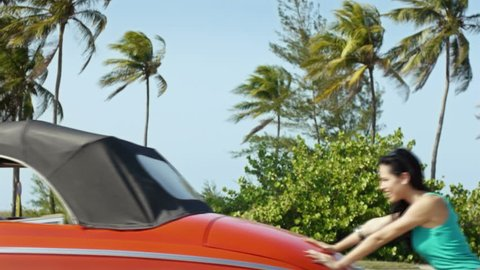 Two beautiful young women laughing while pushing broken down red convertible vintage car