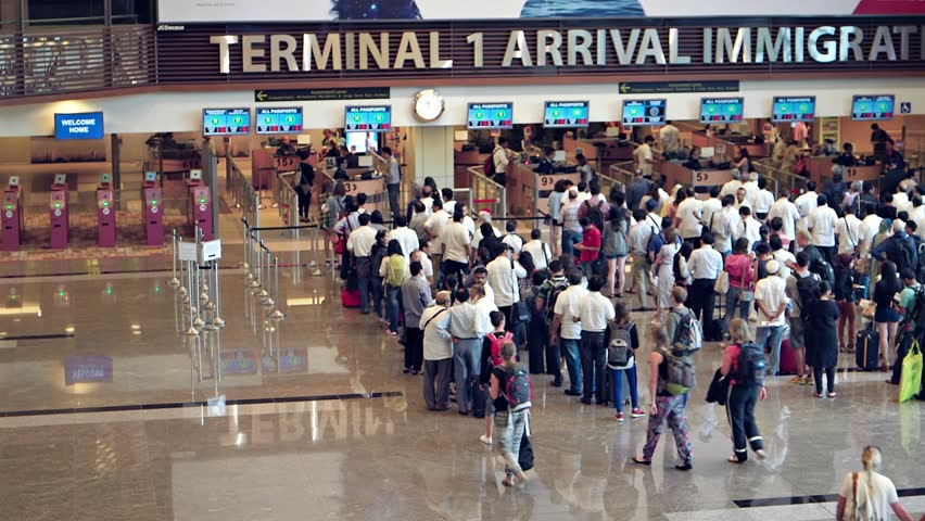 SINGAPORE - CIRCA AUG 2015: Long lines of travelers at the immigration counters of Singapore Changi Airport's Terminal One arrivals area.