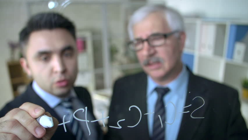 Business mentor and businessman doing calculations on glass board