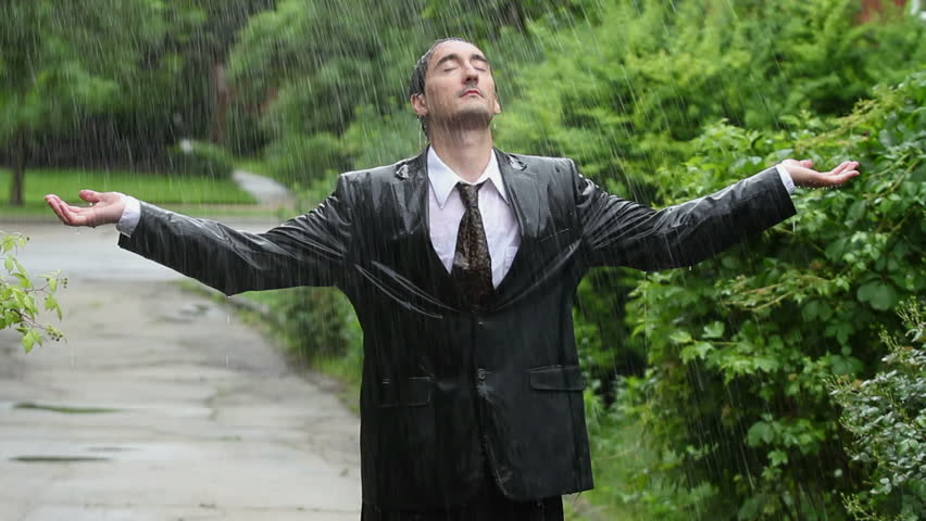 Business man in rain, holding up arms, eyes closed