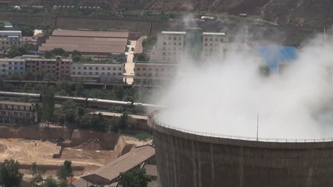 Closeup of a coal fired powerplant in the Chinese city of Lanzhou. A train is passing by in the background.