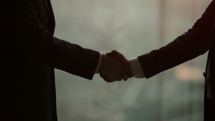 Silhouette of two businessmen talking and shaking hands, standing by the window at sunset, for the construction of a skyscraper and crane in the background, close-up | Shutterstock HD Video #12178607