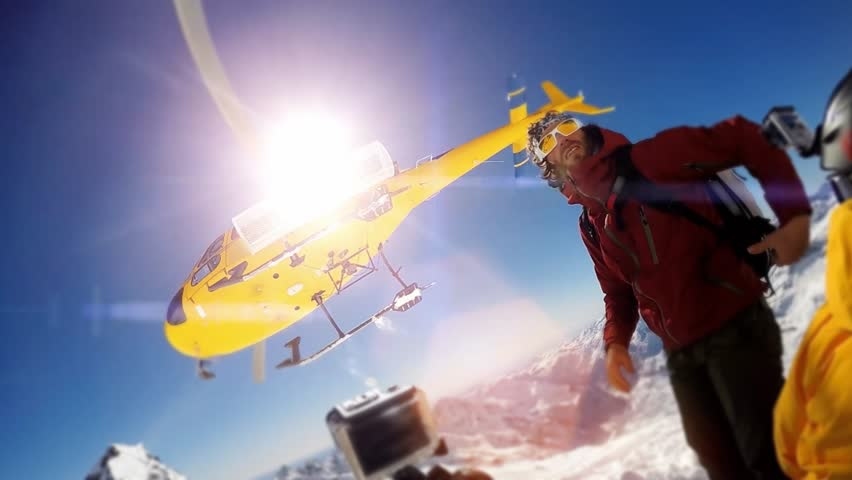 Actionsportlers were dropped by a helicopter at the top of the mountains. The sun is shining brightly in the blue sky. There is a mountain range in the background covered in snow.   Shutterstock HD Video #12186776